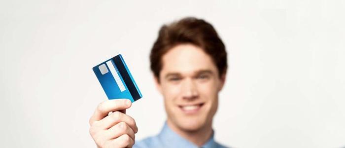 Hombre sostiene su primera tarjeta de crédito